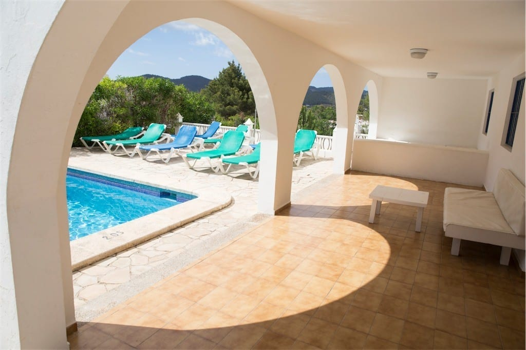 Covered terrace next to pool with views across the country side