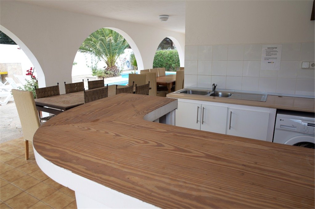 Outside Kitchen and dining area under covered terrace by pool