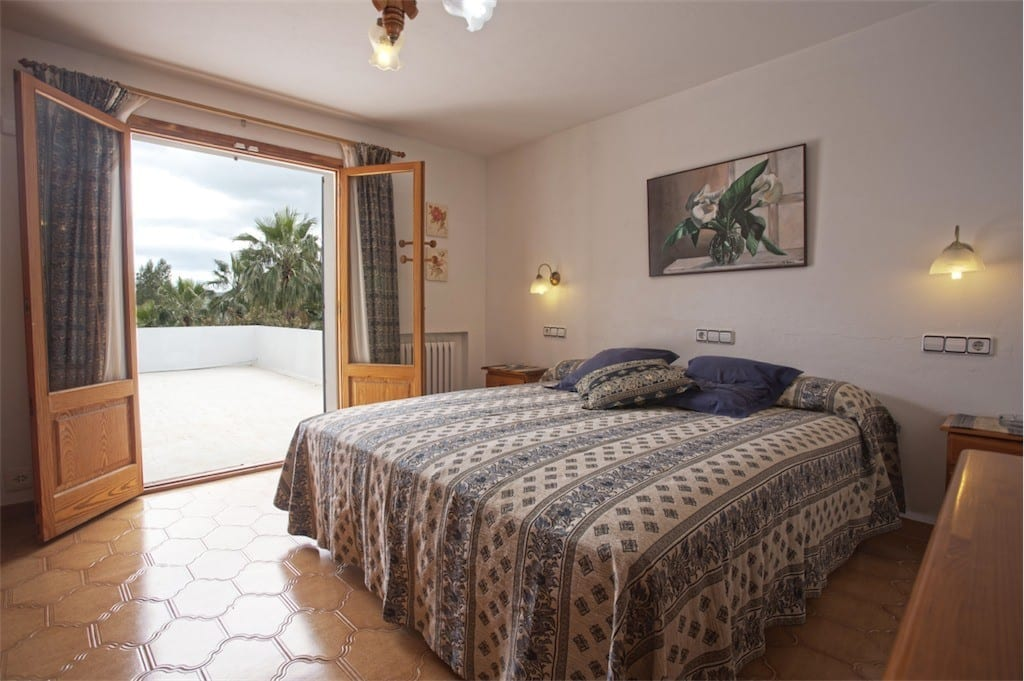 Spacious double bedroom with doors leading to terrace