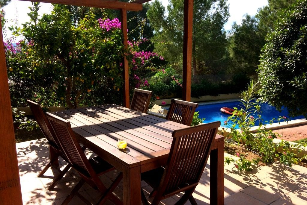 Wooden dining table and chairs on terrace by pool