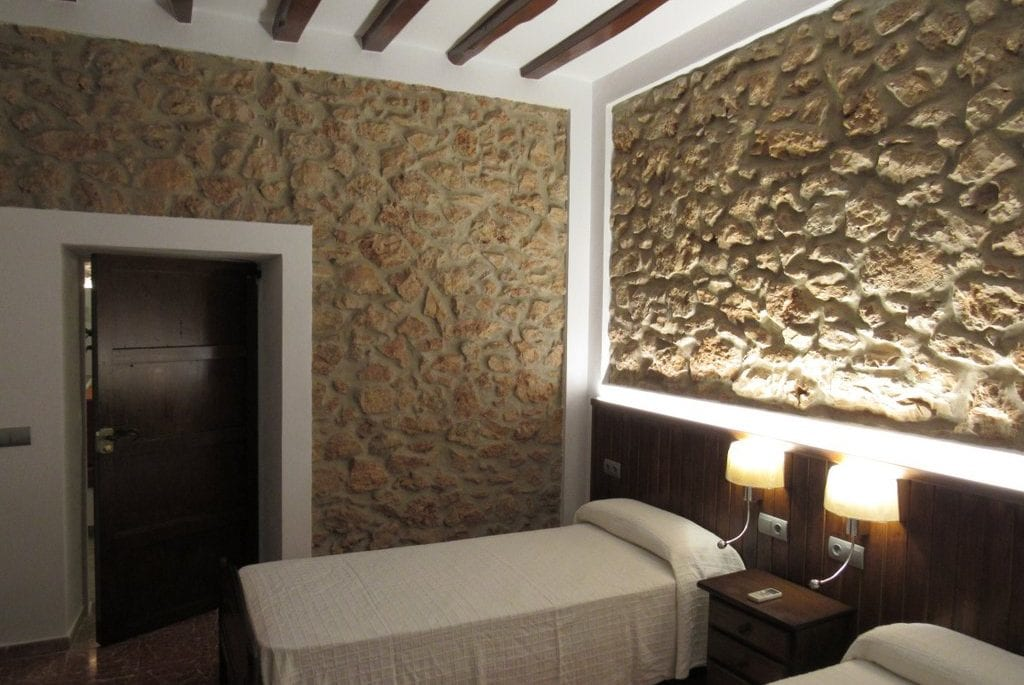 Natural stone walls in twin bedroom