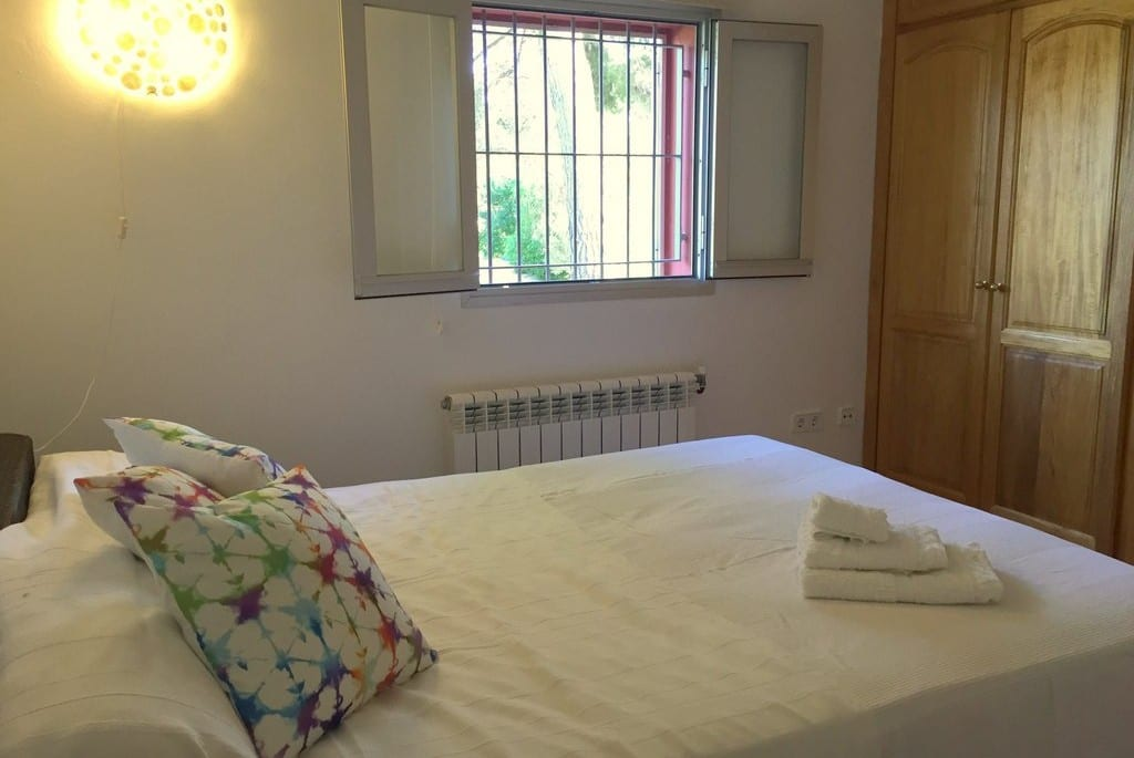 Double bed and wooden wardrobes at Villa Tinto