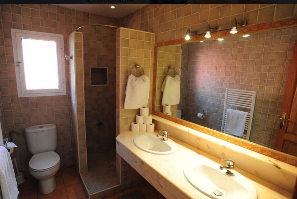 Large tiled shower room and double sink