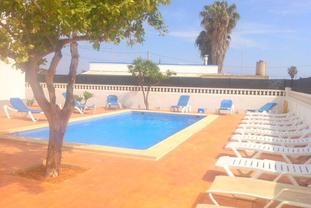Walled pool and terrace with sunloungers at Villa Torres