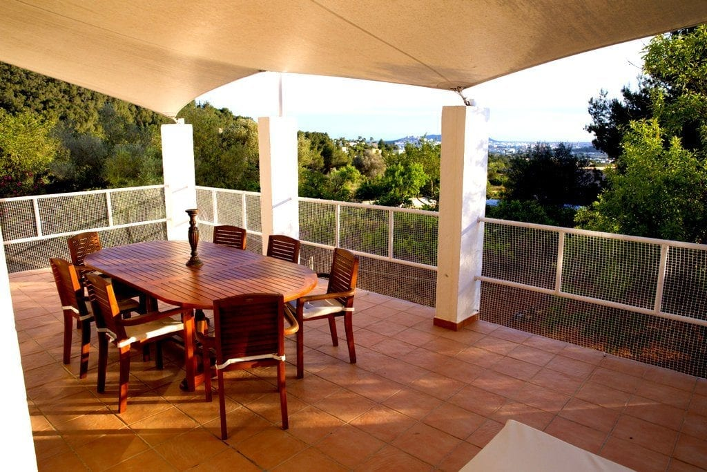 Covered terrace with outside dining table and chairs and views towards Ibiza