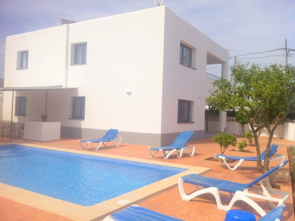 Pool area with sunloungers at Villa Torres